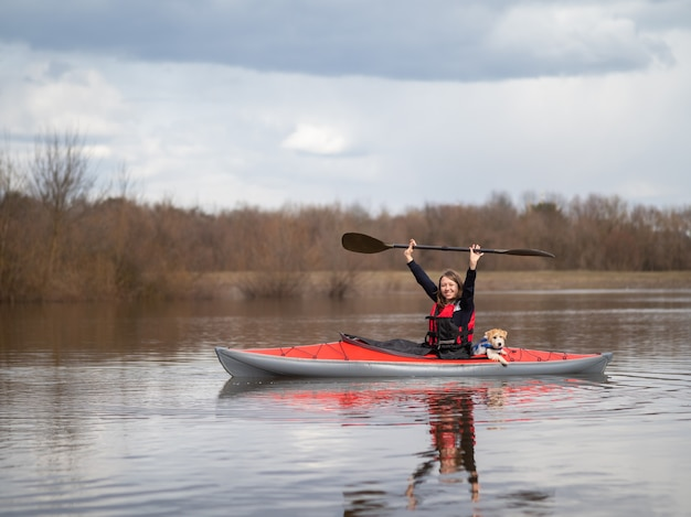 Une fille dans un kayak rouge tenant une pagaie au-dessus de sa tête.
