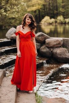 Fille dans une longue robe rouge près du lac dans le parc au coucher du soleil.
