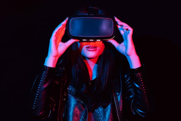 Fille dans des lunettes de réalité virtuelle modernes sur fond noir