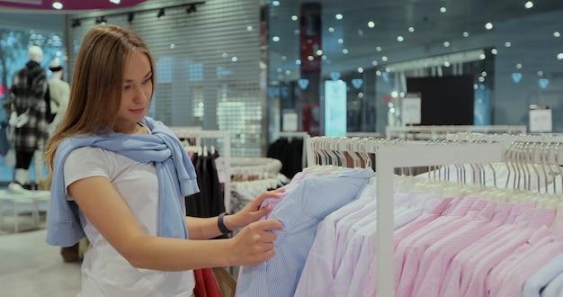 Fille dans un magasin de vêtements choisit une robe. portrait d'une femme accro du shopping dans une boutique de mode.