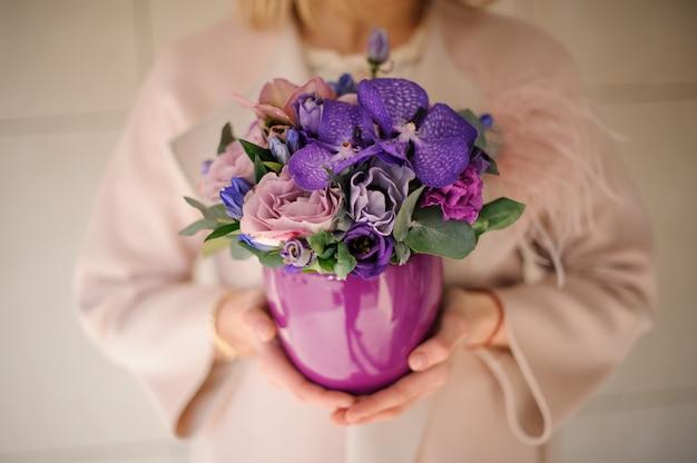 Fille dans le manteau tenant un pot de fleurs violettes de couleur tendre