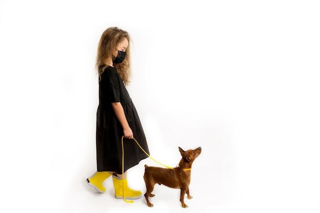Une fille dans un masque antiviral protecteur noir promène le chien. nouvelle réalité de la vie pendant la pandémie de covid-19. précautions en cas de pandémie de coronavirus. voyager avec des animaux de compagnie. photo de haute qualité