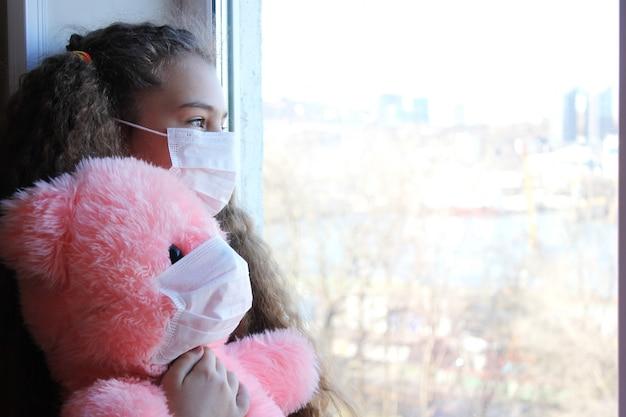 Une fille dans un masque facial et un ours en peluche dans un masque médical regardent la rue par la fenêtre de leur appartement.