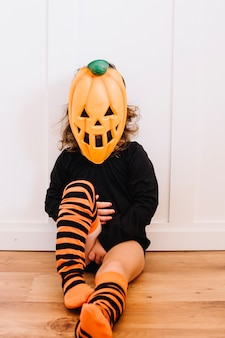 Fille dans un masque de jack-o-lanterne assis sur le sol