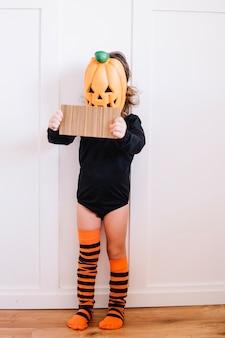 Fille dans le masque de jack-o-lanterne contenant du carton