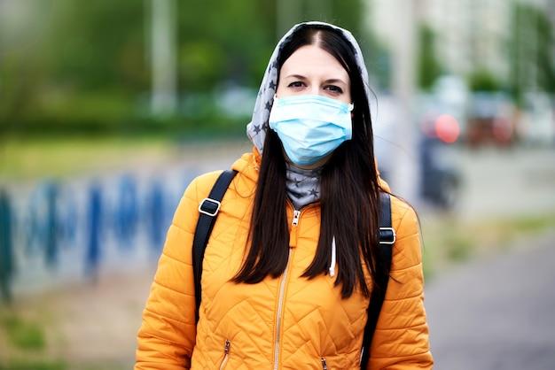 Une fille dans un masque médical, une cagoule et une mallette. dame dans une veste orange