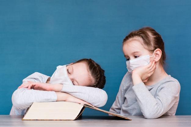 Une fille dans un masque médical en quarantaine dort sur un livre, et une autre fille dans un masque est assise à proximité. éducation des enfants isolés dans une épidémie