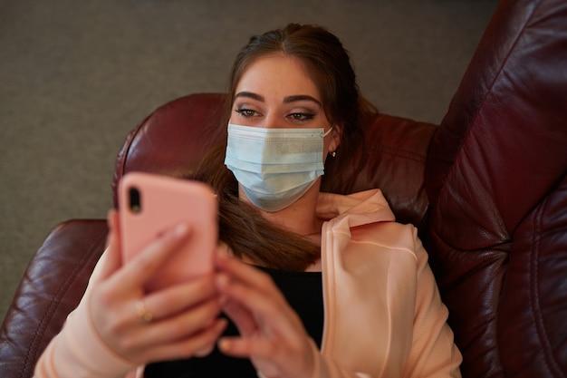 Une fille dans un masque médical avec un téléphone dans ses mains