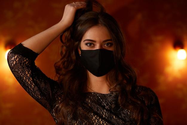 Une fille dans un masque noir ajuste ses cheveux