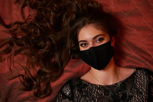 Une fille dans un masque noir est allongée sur le lit