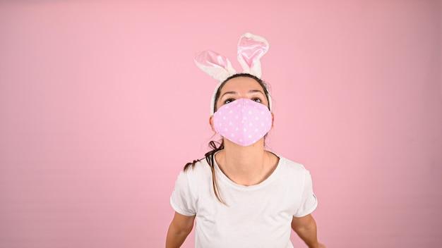 Fille dans un masque avec des oreilles de lapin, sur fond rose. photo de haute qualité