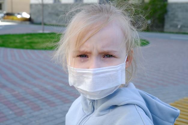 Une fille dans un masque de protection marche dans la rue. l'enfant est bouleversé.