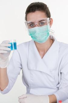 Fille dans un masque tenant un tube à essai avec un liquide bleu