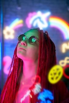 Fille dans des néons, belle femme à lunettes de soleil, aux cheveux roses, avec des nattes de dreadlocks,