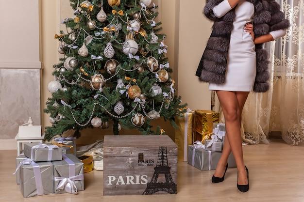 Fille dans la nouvelle année. la figure de la fille en robe et manteau de fourrure debout à l'arbre de noël décoré.