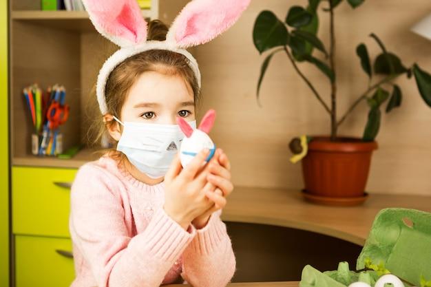 Fille dans les oreilles de lièvre fait un lapin de pâques dans un masque médical à partir d'un œuf et de la pâte à modeler.