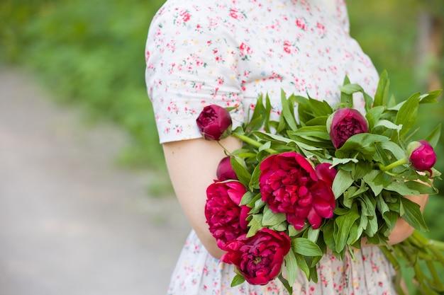Fille dans le parc avec bouquet de belles pivoines rouges dans ses mains