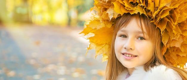 Fille dans le parc avec des feuilles d'automne.