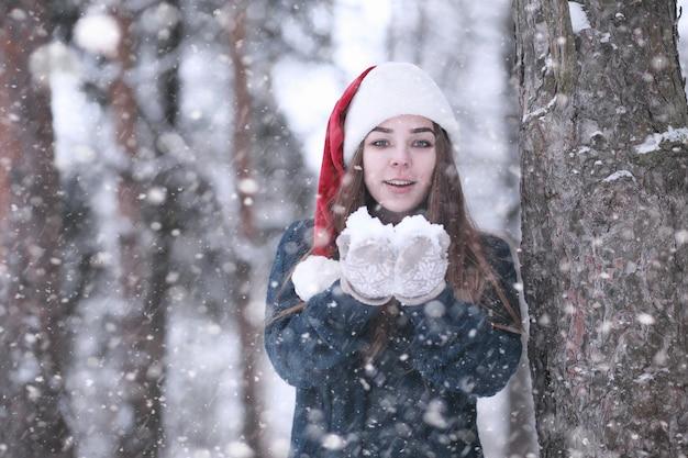 Fille dans un parc d'hiver l'après-midi dans les chutes de neige