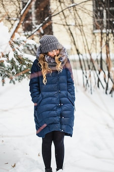 Fille dans un parc d'hiver couvert de neige