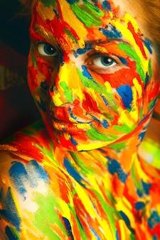 Fille dans des peintures colorées en studio