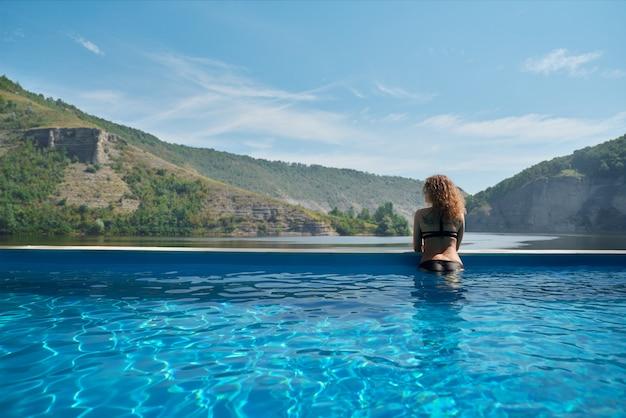 Fille dans la piscine en admirant le paysage.
