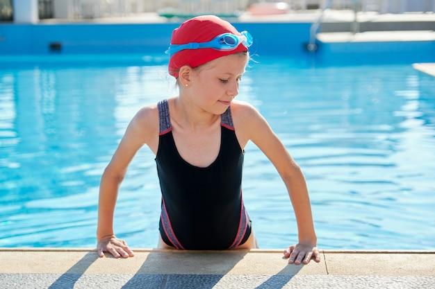 Fille dans la piscine extérieure en bonnet de bain, maillot de bain et lunettes