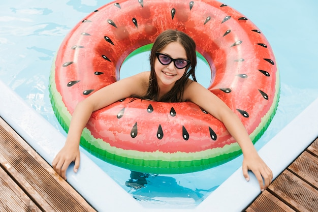 Fille dans la piscine avec floatie melon d'eau