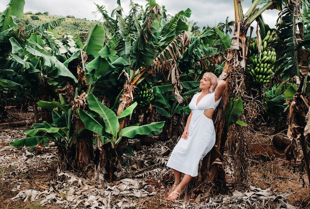 Une fille dans une plantation de bananes sur l'île maurice, une ferme de bananes sur une île tropicale, une fille en robe blanche sur une plantation en afrique