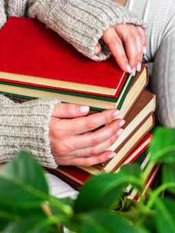 Une fille dans un pull assis sur une couverture avec des livres