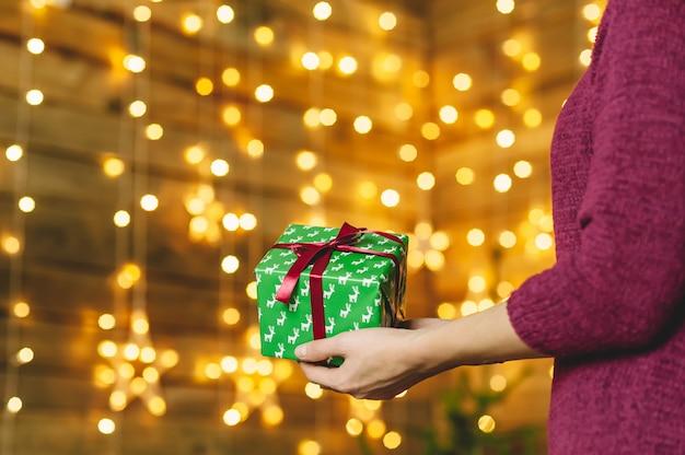 Une fille dans un pull bordeaux, tient dans ses mains un coffret vert avec un ruban rouge. à l'arrière-plan, un mur en bois avec une guirlande d'étoiles. concept sur le thème des vacances.