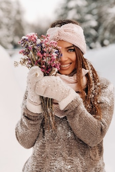 Une fille dans un pull en hiver avec un bouquet dans ses mains se dresse parmi de grandes congères.