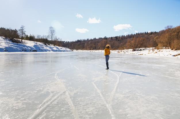 Fille dans un pull jaune et coupe de cheveux courte sur la glace de la rivière.