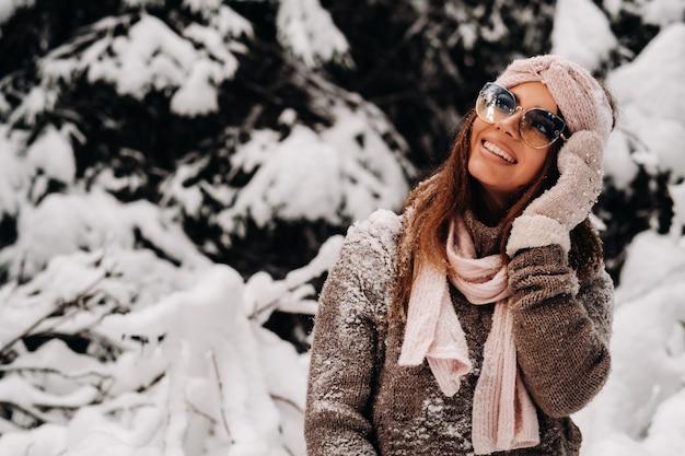 Une fille dans un pull et des lunettes en hiver dans une forêt couverte de neige.