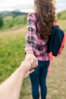Une fille dans un pull rayé rouge tenant l'homme à la main et à la recherche du magnifique paysage de montagnes