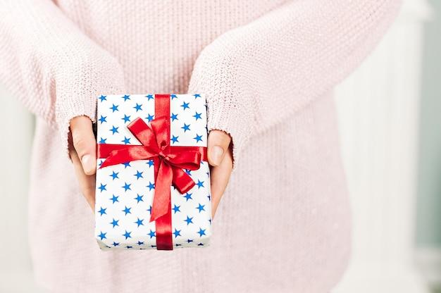 Une fille dans un pull rose tient dans ses mains un cadeau avec des étoiles bleues et un ruban rouge. sur un fond clair. concept sur le thème des vacances.