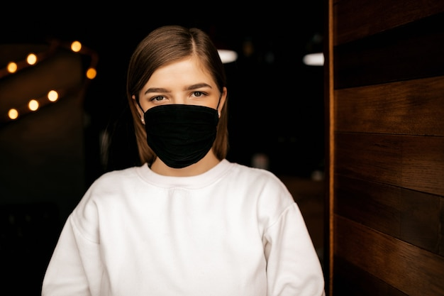 Fille dans un restaurant dans un masque médical noir, regardant la caméra, fond sombre. protection antivirus.