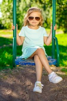 Fille dans une robe bleue et des lunettes de soleil se balançant sur une balançoire
