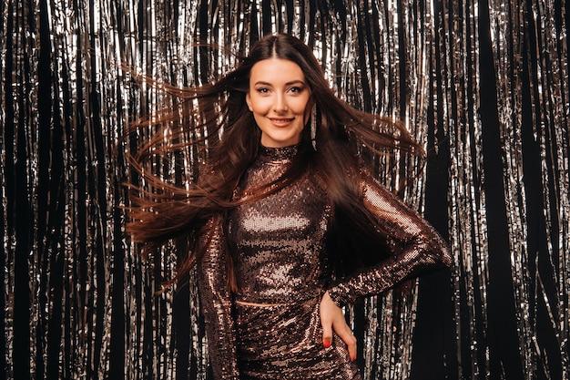 Fille dans une robe brillante sur un fond argenté de pluie du nouvel an avec des cheveux en développement.