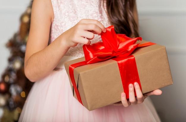 Une fille dans une robe chic se tient avec un cadeau du nouvel an dans ses mains dans le contexte