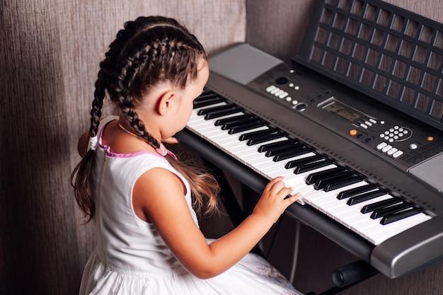 Fille dans une robe d'été blanche joue un synthétiseur électronique