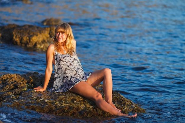 Fille dans une robe d'été mouillée sur les rochers