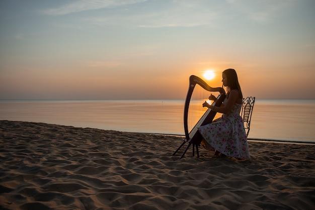 Une fille dans une robe à fleurs joue sur une harpe celtique au bord de la mer au coucher du soleil