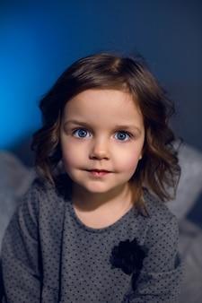 Fille dans une robe grise est assise sur un lit avec des oreillers dans une chambre avec un mur bleu