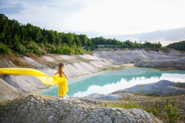 Fille dans une robe jaune avec des ailes dans un tissu jaune près du lac
