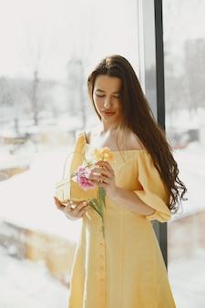 Fille dans une robe jaune avec un panier dans ses mains célèbre pâques