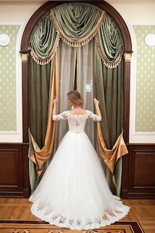Fille dans une robe de mariée blanche près de la fenêtre. belle femme dans une robe de mariée blanche avec beau maquillage et coiffure. ouverture des rideaux de fenêtre.