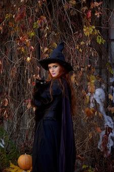 Une fille dans une robe noire et un chapeau de sorcière à l'halloween avec un chat noir dans le parc