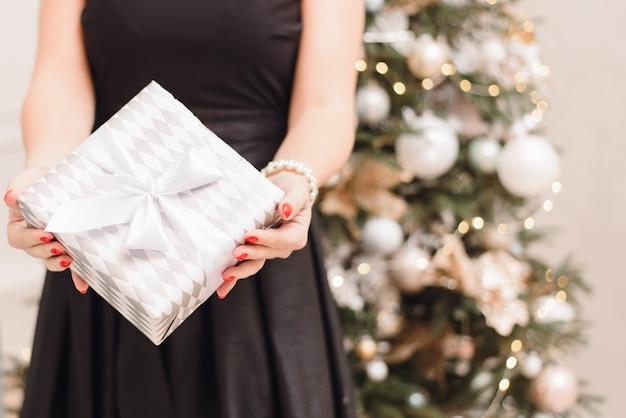 Fille dans une robe noire festive sur le fond d'un arbre de noël avec bokeh détient un cadeau