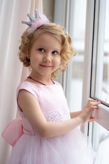 Fille dans une robe rose et une couronne sourit près de la fenêtre